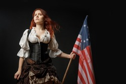 Girl in historic dress from United States Revolutionary War with flag. July 4th, Independence Day USA Concept Photo Composition
