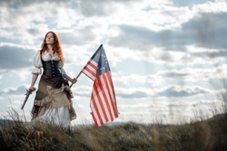Girl in historical dress of 18th century with flag of United States. July 4 is US Independence Day. Woman of patriot freedom fighter in outdoor on background cloudy sky