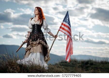 Girl in historical dress of 18th century with flag of United States. July 4 is US Independence Day. Woman of patriot freedom fighter in outdoor on background cloudy sky Stock photo ©