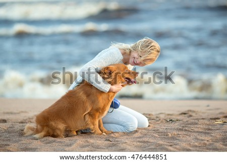 girl in jeans and a blue sweater sitting with his dog on the sand by the sea