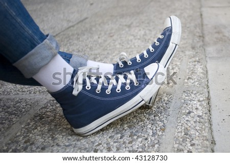 Girl in jeans and blue sneakers.