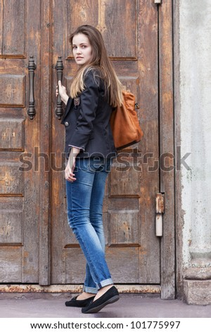 Girl in jeans opens the door to the old church