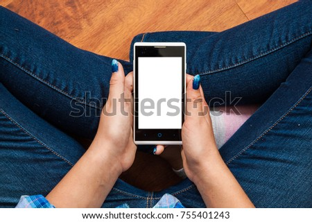 girl in jeans sits on the floor and holding a smartphone. Concept of teenage life and gadgets. Top view #755401243