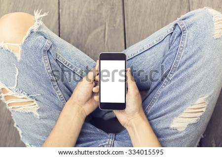 Girl in jeans with blank smartphone on the wooden floor, mock up #334015595