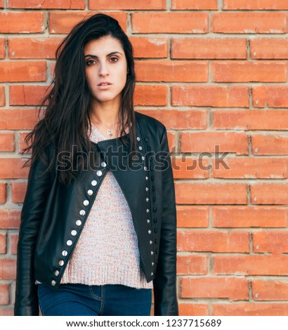 girl in leather jacket on brick wall background upset #1237715689
