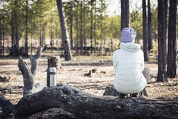 Girl in light jacket and hat is sitting and resting after hike in the woods on snake next to thermos of tea.