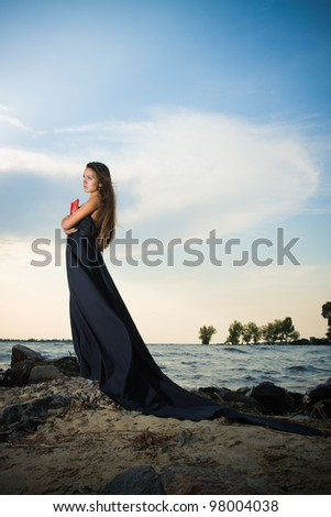 Girl in long dress thought with a book at the shoreline