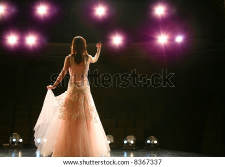 girl in long gown performing on stage - stock photo