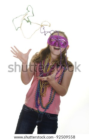 Girl in mask catching mardi gras beads