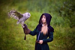 girl in medieval dress is holding an owl on her arm