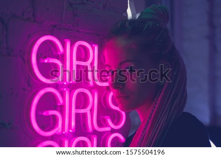Girl in neon lights  in nightclub, beautiful woman, with long pink hair, with dreadlocks pigtails, bright trendy  stylish 80s, neon word Girls on the wall