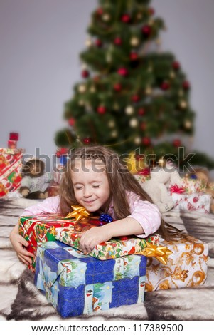Girl in pajamas lying under the Christmas tree with gift in hand