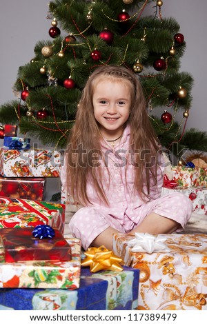 Girl in pajamas sitting under the Christmas tree with gift in hand