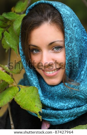 Girl in park colourful autumn. Beautiful lady in headscraft and vivid foliage