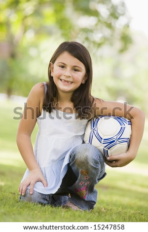 Girl in park holding football looking to  camera