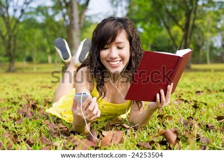 Girl in park with book and portable music device