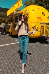 Girl in pink sunglasses in a gray sweater and blue jeans posing near a food truck with a pink milkshake. Sunny, natural light. The average plan.