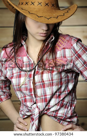 Girl in plaid shirt and cowboy hat against a wooden wall