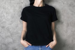 Girl in plain black shirt and jeans on concrete backgroud. Mock up