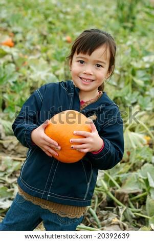Girl in Pumpkin Patch holding a Pumpkin