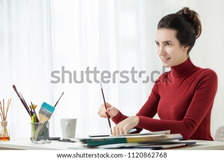 girl in red clothes is sitting in the office. One young woman only. artist's workplace