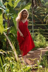 Girl in red dress are walking on green area in Bali. Rice terrace