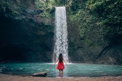 Girl in red dress at amazing Tibumana Waterfall Bali - the best cascade in Indonesia