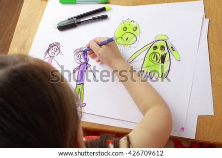Girl in red dress draws a picture of the family. children\'s fears, bad dreams, nightmares.