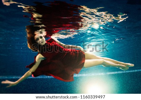 girl in red dress swims under blue water in pool #1160339497