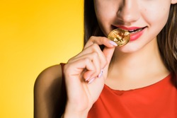 girl in red dress tries golden bitcoin to taste, on yellow background
