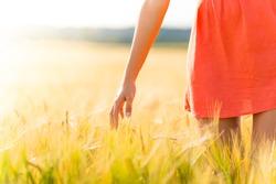Girl in red dress walking on wheat field. Harvest theme.
