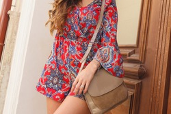 Girl in red dress with beige leather handbag on the shoulder. Woman in summer overall in the city on sunny summer day. Vogue woman with long blonde hair near wooden door