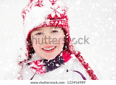 Girl in red hat under snow falling