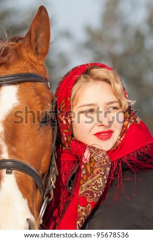 Girl in red headscarf and Russian Don horse at winter day