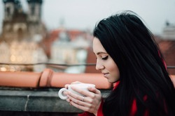 Girl in red with a cup of coffee sits in a cafe in Prague