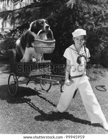 Girl in sailor suit pulling dog in basket