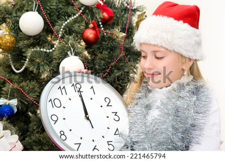 Girl in santa hat considers minutes before the start of Christmas holding in hands clock
