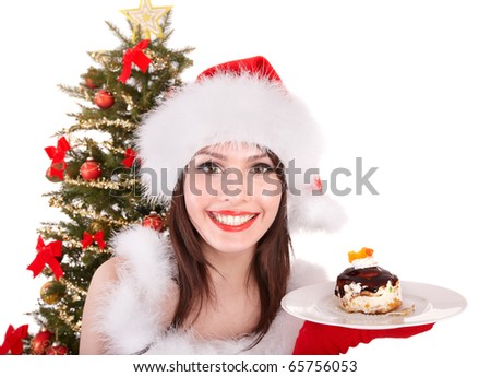Girl in santa hat eat cake on plate by christmas tree.. Isolated.