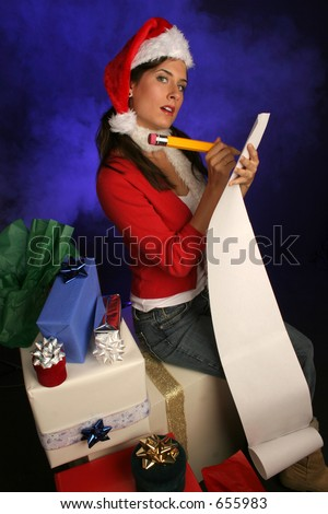 girl in santa hat is checking her list for the holidays surrounded by gifts in a misty blue background
