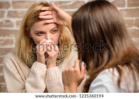 Girl in scarf hold tissue while doctor examine her. Recognize symptoms of cold. Remedies should help beat cold fast. Cold and flu remedies. Tips how to get rid of cold. Woman feels badly ill sneezing.