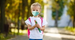 Girl in school uniform with air pollution mask on face, looks at camera standing in front of school
