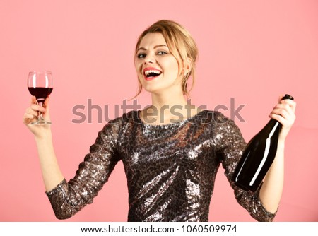 Girl in shining dress with alcohol on pink background. Lady holding glass and bottle of red Italian wine. Winetasting or party concept. Woman with smiling face drinks expensive cabernet or merlot. #1060509974