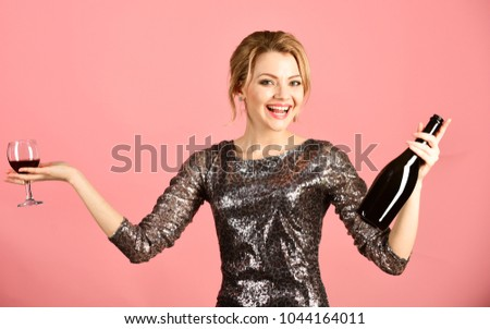Girl in shining dress with alcohol on pink background. Winetasting and alcohol concept. Woman with smiling face drinks expensive cabernet or merlot. Lady holding glass and bottle of red Italian wine. #1044164011