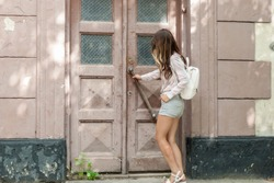 girl in short shorts with a backpack opens the old door in the thrown house
