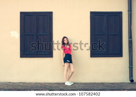girl in shorts and red t-shirt standing in front of house between two closed windows summer day