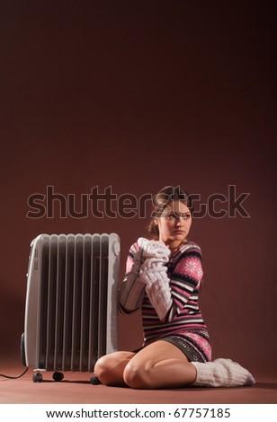 girl in socks heats the radiator - stock photo