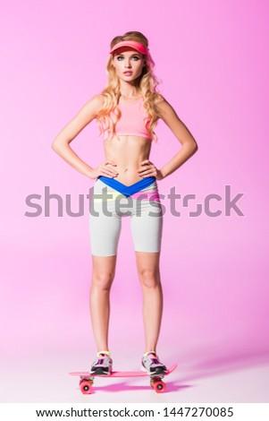 girl in sportswear posing on penny board on pink, doll concept