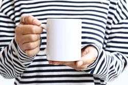 Girl in  striped sweatshirt holding white coffee mug , white porcelain mug mock up. 11 oz mockups