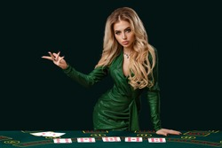 Girl in stylish dress is showing something, leaning on playing table with cards on it, posing on green background. Poker, casino. Close-up, copy space