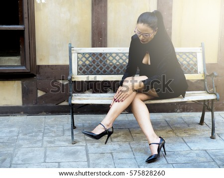 girl in stylish fashion footwear is on the sidewalk in the city #575828260